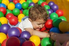 Fille aidant son petit frère sortant une piscine de boule Photographie stock libre de droits