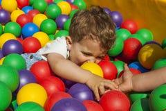 Fille aidant son petit frère sortant une piscine de boule Images libres de droits