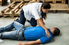 Fille aidant un homme inconscient Image stock