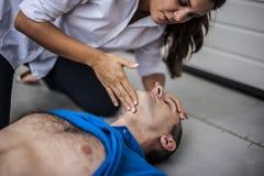 Fille aidant un homme inconscient photo stock