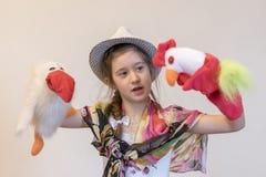 Fille 8 ans dans un chapeau jouant des poupées de chiffon Spectacle de marionnettes Corneille et coq Jouets créatifs Images stock