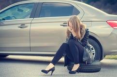Fille appelle Voiture cassée sur un fond La femme s'asseyent sur une roue Réparation sexy de jeune femme une voiture Fond naturel Images libres de droits