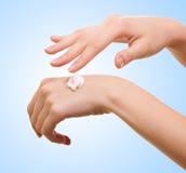 Fille appliquant de la lotion blanche sur sa main images stock