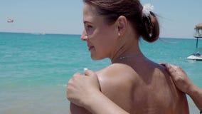 Fille appliquant la crème de protection du soleil sur la plage 4K banque de vidéos