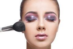 Fille appliquant le cosmétique utilisant la brosse de maquillage Image libre de droits