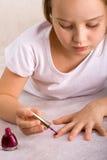Fille appliquant le vernis à ongles Photographie stock libre de droits