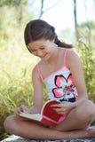 Fille appréciant la lecture Photos stock
