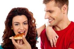 Fille appréciant la partie de pizza partagée par son ami Photographie stock libre de droits