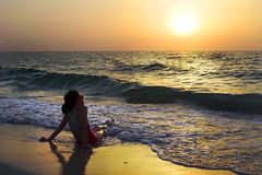 Fille appréciant le coucher du soleil à l'océan image stock