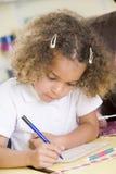 Fille apprenant à écrire des numéros dans la classe primaire Image libre de droits