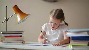 Fille apprenant des leçons, fille mignonne faisant son travail, écolière studing à la maison à la table clips vidéos