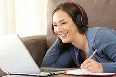 Fille apprenant sur la ligne cours audio de écoute image stock