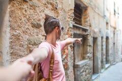 Fille après l'ami tenant des mains dans la vieille rue européenne riant et souriant Image libre de droits