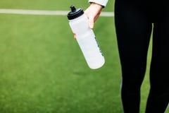 Fille après la formation, le fonctionnement ou les sports un repos dans le premier plan, une bouteille de l'eau La fille travaill photographie stock libre de droits