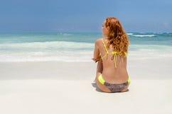 Fille arrière sur la plage photographie stock libre de droits
