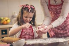 Fille arrosant la farine au-dessus de la table de cuisine image stock