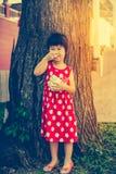 Fille asiatique adorable mangeant la crème glacée pendant le jour d'été outdoors Photo libre de droits