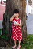 Fille asiatique adorable mangeant la crème glacée pendant le jour d'été outdoors Photographie stock
