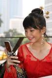 Fille asiatique attirante au téléphone Photographie stock libre de droits
