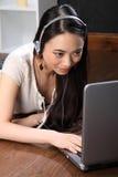 Fille asiatique avec des écouteurs utilisant le skype sur l'ordinateur portatif Photo libre de droits