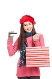 Fille asiatique avec le chapeau de Noël, la carte de crédit et le panier rouges Image libre de droits