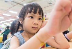Fille asiatique avec une tablette tactile de main dans la salle de classe Photo stock