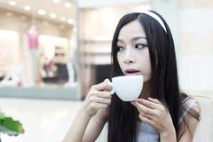 Fille asiatique ayant le café Image stock
