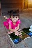 Fille asiatique belle de plan rapproché souriant et lisant l'album de photo E Image stock