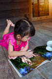 Fille asiatique belle de plan rapproché souriant et lisant l'album de photo E Image libre de droits