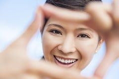 Fille asiatique chinoise de femme faisant le cadre de doigt Photo libre de droits
