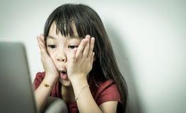 Fille asiatique choquée par ce qu'elle voient sur l'écran d'ordinateur images libres de droits