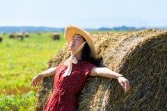 Fille asiatique détendant dedans dans un domaine de blé portant la robe rouge image stock