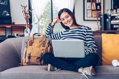 Fille asiatique d'adolescent employant l'ordinateur portable et la musique de ?coute sur le sofa avec le visage de sourire heureu image libre de droits