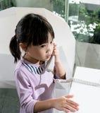 Fille asiatique d'enfant à l'aide du téléphone de fil sur le bureau blanc Photo stock