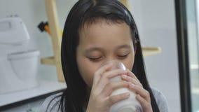 Fille asiatique d'enfant buvant du lait sur le bureau, concept confortable d'enfants à la maison banque de vidéos
