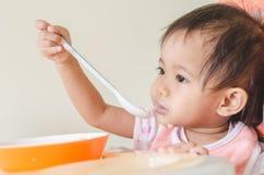 Fille asiatique d'enfant en bas âge mangeant des céréales avec du lait sur la chaise d'arbitre au hom photo stock