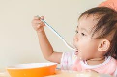 Fille asiatique d'enfant en bas âge mangeant des céréales avec du lait sur la chaise d'arbitre au hom photographie stock libre de droits