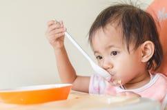 Fille asiatique d'enfant en bas âge mangeant des céréales avec du lait sur la chaise d'arbitre au hom images libres de droits