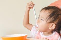 Fille asiatique d'enfant en bas âge mangeant des céréales avec du lait sur la chaise d'arbitre au hom photographie stock