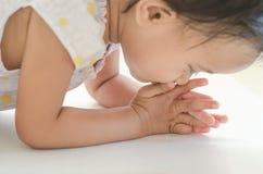 Fille asiatique d'enfant en bas âge prosternée à l'aîné pour des mercis image stock