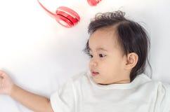 Fille asiatique d'enfant en bas âge se trouvant sur le lit à la maison photographie stock