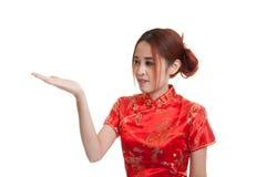 Fille asiatique dans l'espace vide de cheongsam de présent chinois de robe avec h Image libre de droits