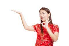 Fille asiatique dans l'OK chinois d'exposition de robe de cheongsam avec l'espace vide Image stock