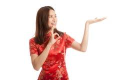 Fille asiatique dans l'OK chinois d'exposition de robe de cheongsam avec l'espace vide Photographie stock libre de droits