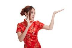 Fille asiatique dans l'OK chinois d'exposition de robe de cheongsam avec l'espace vide Photos stock