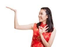 Fille asiatique dans l'OK chinois d'exposition de robe de cheongsam avec l'espace vide Images stock