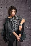 Fille asiatique dans un T-shirt rayé se reposant sur le tabouret de bar photos stock