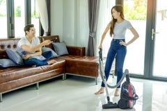 Fille asiatique de couples faisant le nettoyage de plancher avec le whil de décapant de vaccuum Photos stock