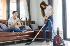 Fille asiatique de couples faisant le nettoyage de plancher avec le whil de décapant de vaccuum Image stock