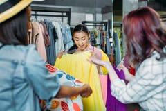 Fille asiatique de hippie avec des amis choisissant des vêtements dans la boutique Photo stock
